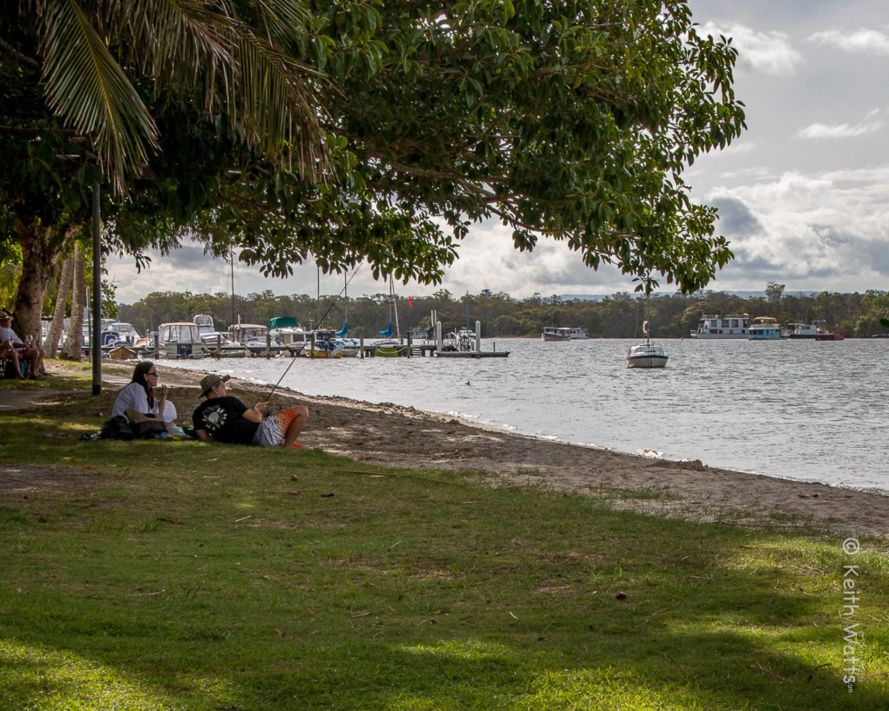 A family take time out to relax and maybe catch a fish or two at Noosaville on the Sunshine Coast